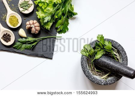 spices for cooking and fresh salad with pounder on white background top view