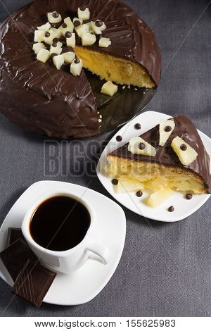 Homemade chocolate-glazed pineapple cake with one slice on white plate and a cup of coffee with three pieces of chocolate on grey background