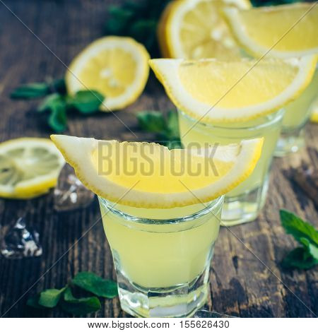 Traditional homemade lemon liqueur limoncello and fresh citrus on the old wooden background. Italian traditional liqueur limoncello with lemon. Italian alcoholic beverage. Selective focus. Square.