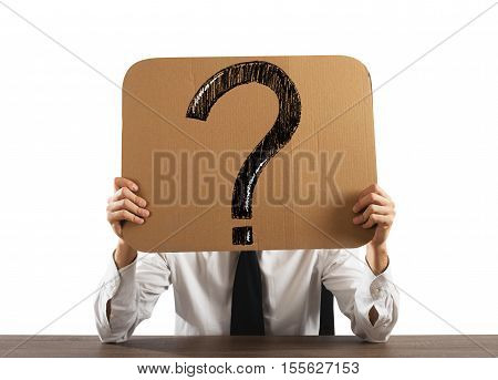 Businessman in the office holds a cardboard with big question mark