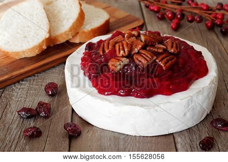 Brie Topped With Cranberry Sauce And Pecans On A Rustic Wooden Background