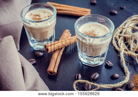 Espresso liqueur on a table. Irish creme liqueur on dark background with coffee beans and cinnamon. Shot glass of creamy coffee liqueur with coffee beans. Alcoholic bavarage concept. Selective focus.