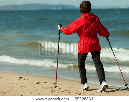 Nordic walking. Woman hiking on the beach. Active and healthy lifestyle.