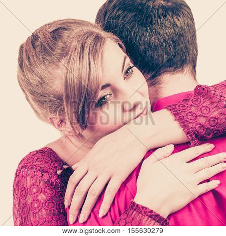 Couple hugging. Woman is sad and being consoled by his partner. Man comforting his girlfriend. Troubled girl and her boyfriend. Filtered photo