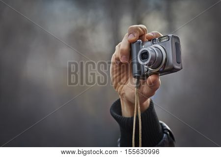 Adult man hand holding a compact digital point-and-shoot photo camera over grey out of focus outdoor background with copy space. Taking outdoor pictures with a digital compact camera.