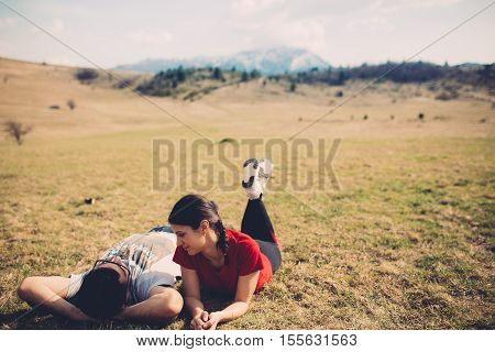 Loving couple resting in nature. Spending free time together. Enjoying the holidays. Lying on a meadow.Pair spending time in nature.Camping and having picnic