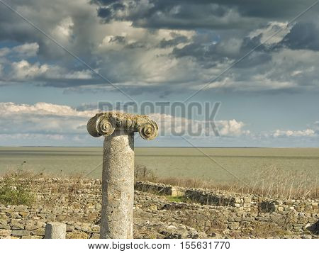 A dramatic blue sky with white clouds over the ruins of an ancient greek column at Histria, on the shores of Black Sea. Histria is the oldest urban settlement on Romanian territory