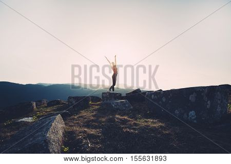 Active living concept. Exercise for healthy living. Young girl hiking on mountains. Standing on top of mountain at sunset.Fitness, achievemnt,celebrating concept.Being on top of the world