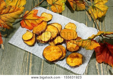 Sweet potato and potato chips on a white paper with fall background