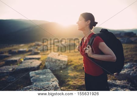 Young traveler hiking at sunset. Active living concept. Enjoying holidays. Spending time in nature.Fitness, achievemnt,celebrating concept.Being on top of the world
