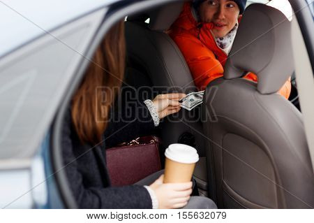 Young girl sends driver in orange coat money for travel sitting in taxi