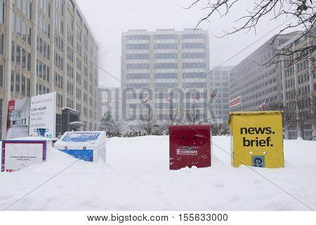 Washington D.C. USA - January 23 2016: boxes with free newspapers covered with snow during a snowstorm.