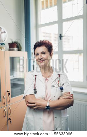 Portrait of experienced doctor smiling. Sympathetic and kind practitioner. Healthcare concept.Older senior retiring doctor being retired from hospital.Trust and relience in general practitioner