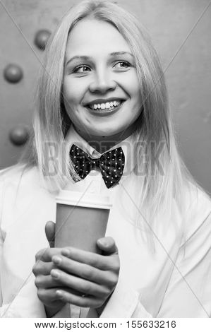 Portrait of beautiful girl with paper cup of coffee in white shirt. black-white photo