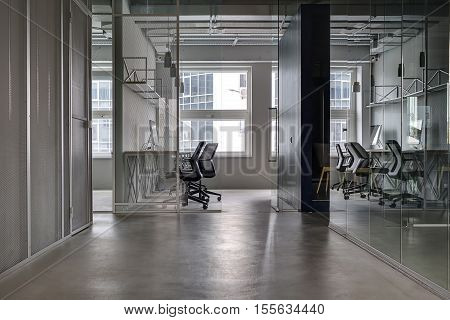 Business interior in a loft style with gray walls and gray floor. There are workplaces with black armchairs and tabletops with computers. They divided with black wall and glass partitions and doors.