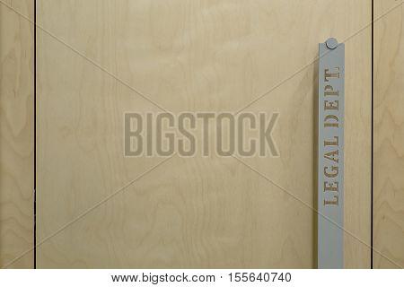 Macro photo of the door handle. On the handle there is an inscription Legal Dept. Door is wooden. Horizontal.