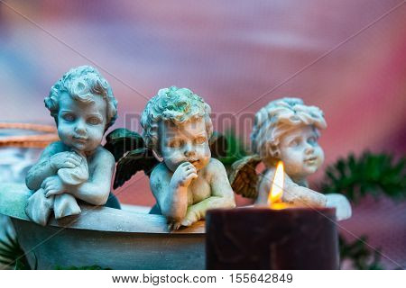 Christmas scene with kitsch putti and lighted candle and fir branch for holiday concept gift business greeting cards