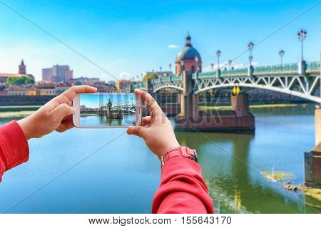 Smartphone photographing the Saint-Pierre bridge passes over the Garonne and it was completely rebuilt in 1987 in Toulouse Toulouse France