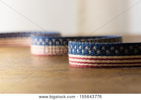 Background for American election or commemorative event. A textile with stars and stripes pattern on old rustic wooden table. Extremely shallow depth of field.