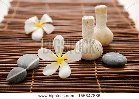 frangipani with massage oil and massage ball ,stones on green bamboo mat