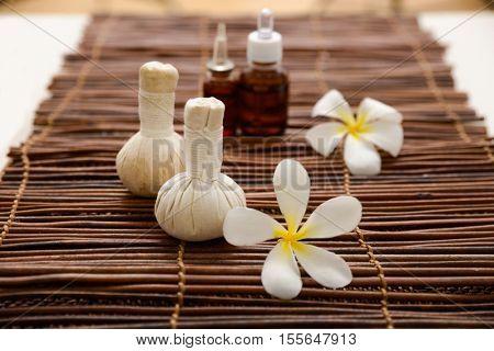 frangipani with massage oil and massage ball on green bamboo mat