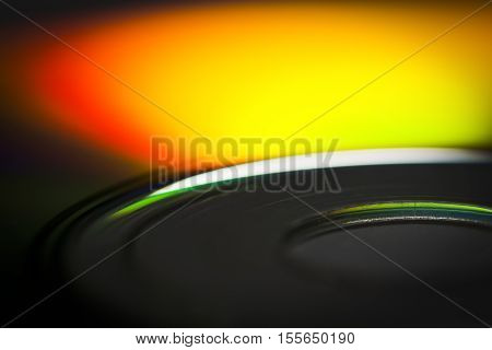 The surface of the CD close-up reflects the spectral colors.