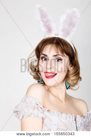beautiful young woman in pink dress and rabbit ears, standing, posing