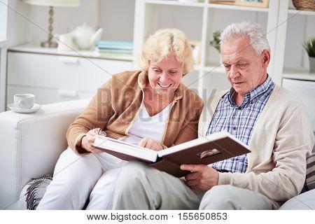 Elderly couple looking through family photo album