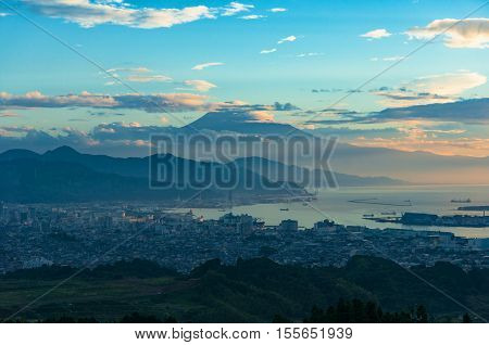 Aerial view of Mt Fuji Shizuoka city coastline and Suruga bay on sunrise. Japanese landscape of urban and farmlands against iconic volcano on the background. Japan