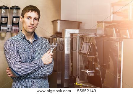 Man going to repare coffee machine in cafe.