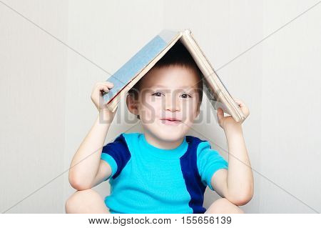 Happy Boy Making Roof With Book