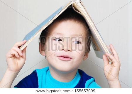 Smiling Boy Looking Right With Book Roof