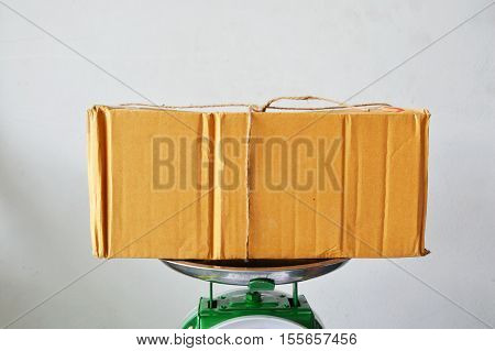 brown paper postbox on weighing scale tray in shop