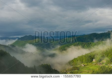 Mountain Forest With Fog Against Dramatic Sky On The Background