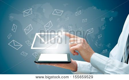 The concept of email marketing. Businessman makes sending emails from your tablet