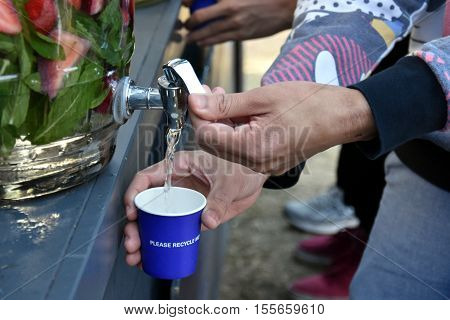 Man's hand unscrews the faucet which drops the fresh water into a glass. Filling A Glass Of Water From Tap. Jugs full of with water and fruits orange strawberry lemon.
