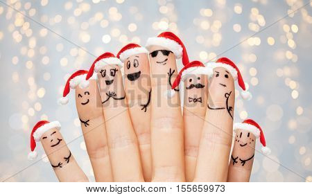 christmas, holidays, family, people and body parts concept - close up of two hands showing fingers with smiley faces and santa hats over lights background
