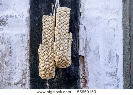 a pair of plaited straw shoes hangs on the wall