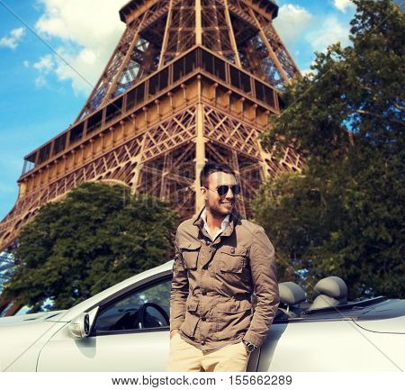 travel, tourism, road trip, transport and people concept - happy man near cabriolet car over paris eiffel tower background