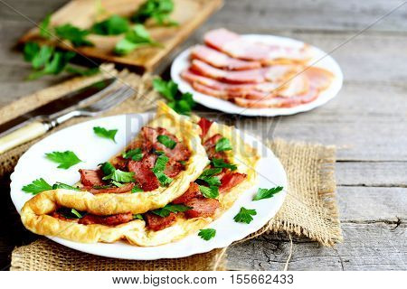 Fried bacon omelette. Delicious omelette with bacon and parsley on a plate, bacon slices on a plate, fork, knife, cutting board, fresh parsley sprigs on old wooden background. Vintage style