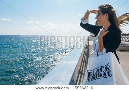 Stylish woman looking far away while standing at seaside and holding Black Friday bags. Conceptual