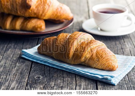 Tasty buttery croissant on old wooden table.