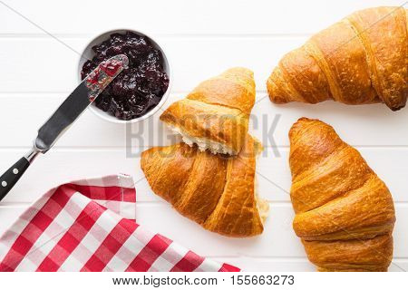 Tasty buttery croissant and jam in jar. Top view.