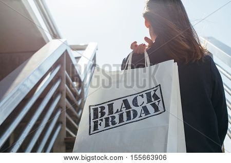 Rear view of incognito brunette holding Black Friday shopping bag while standing outdoors.