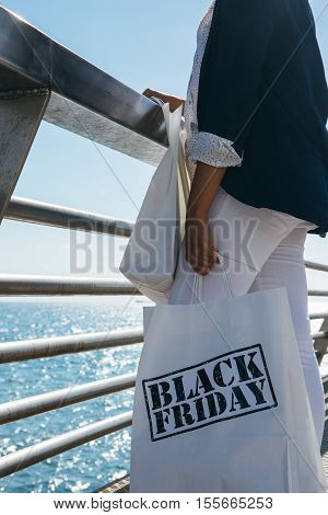 View of stylish female holding Black Friday paper bags while standing at sea front.