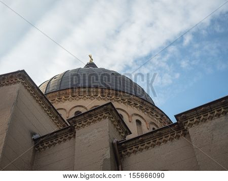 Picture of the dome of the cathedral from below. Building with dark dome and sculpting on the light-beige coloured wall. Holy Cross on the dome of the cathedral.
