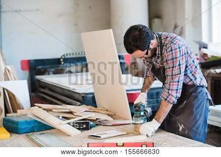 Carpenter with power grinder at his workshop.