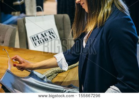 Close up view of incognito woman holding grey top in shop. Black Friday. Cropped view