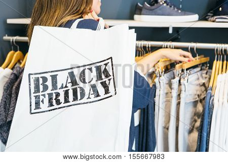 Costumer choosing jeans in the store holding bag with Black Friday sign over shoulder. Cropped view