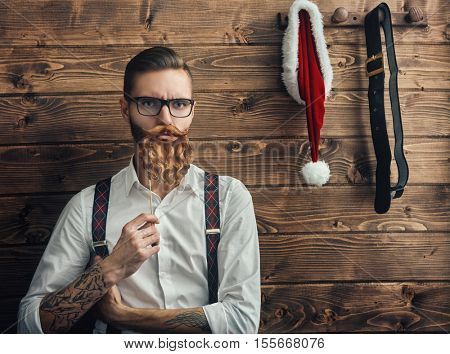 Merry Christmas and Happy Holidays! Handsome man with Santa symbol. Hipster young Santa Claus concept.